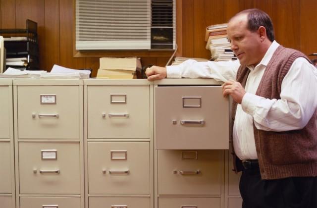 Mitarbeiter stehet vor einem großen Aktenschrank