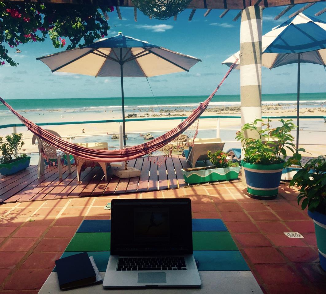 Digitale Nomaden nehmen den Laptop mit an den Strand