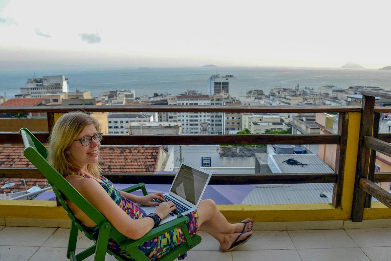 Ute mit Laptop auf dem Balkon in einer Favela in Rio
