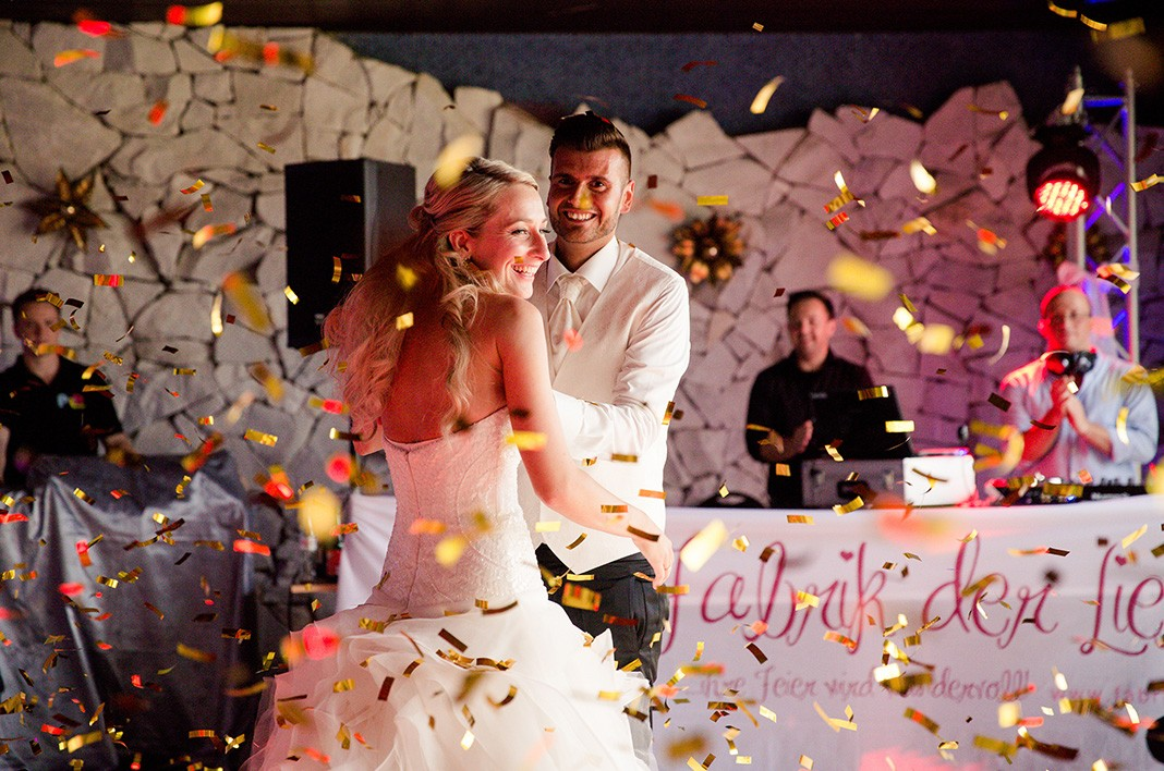 Glückliches Brautpaar tanzt vor einem Fabrik der Liebe Banner