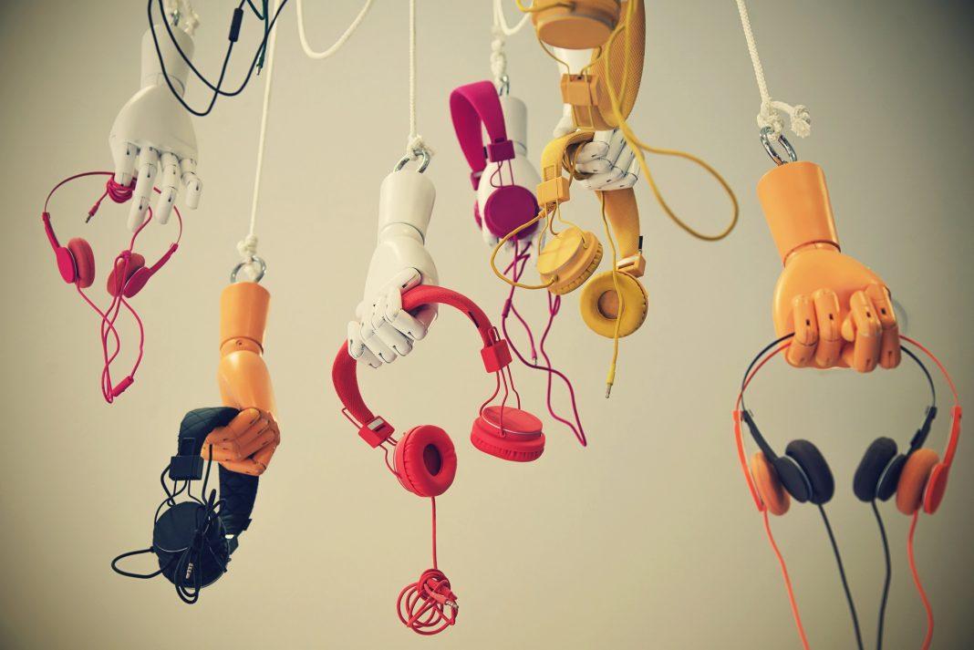 Bunte Kopfhörer werde von Puppenhänden gehalten und hängen herab