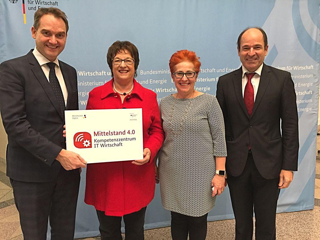 Bundeswirtschaftsministerin Brigitte Zypries überreicht dem BITMi-Vorstand Oliver Grün (links), Andera Gadeib (2. v. r.) und Martin Hubschneider (rechts) den Bescheid für das Mittelstand 4.0-Kompetenzzentrum IT-Wirtschaft