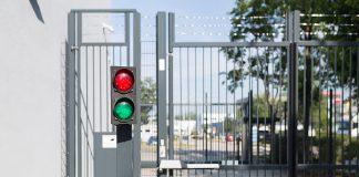 Ampel mit rotem und grünem Signallicht vor Schranke und Gittertor. Links davon die Wand eines Rechenzentrums das mit einer Kamera überwacht wird. as Gittertor ist geschlsosen