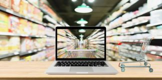 Dgitalisierung im Handel, dargestellt durch aufgeklappten Laptop zwischen Supermarktregalen. Laptopmonitor und Realität zeigen den Flur zwischen den Regalen und zeigen einen realen Einkaufwagen.