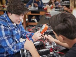 Zwei Kids experimentieren an technischem Gerät und messen Strom bzw. die Spannung.