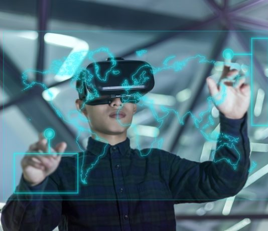 Mann mit VR Brille steht vor Glasscheibe, auf der mit grünen Linien eine Weltkarte gezeichnet ist. Der Mann berührt mit seinen Fingern die Karte. Sein Aussehen lässt darauf schließen, dass der Mann dem asiatischen Kulturkreis zuzurechnen ist.