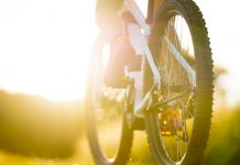 close up part of electric mountainbike sport female legs shoes summer sunny backlight rural landscape tyre