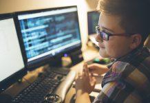 Junge mit Brille und kariertem Hemd, rechts im Anschnitt, vor zwei Computerbildschirmen. Auf dem rechten Bildschirms sind Codes zu erkennen