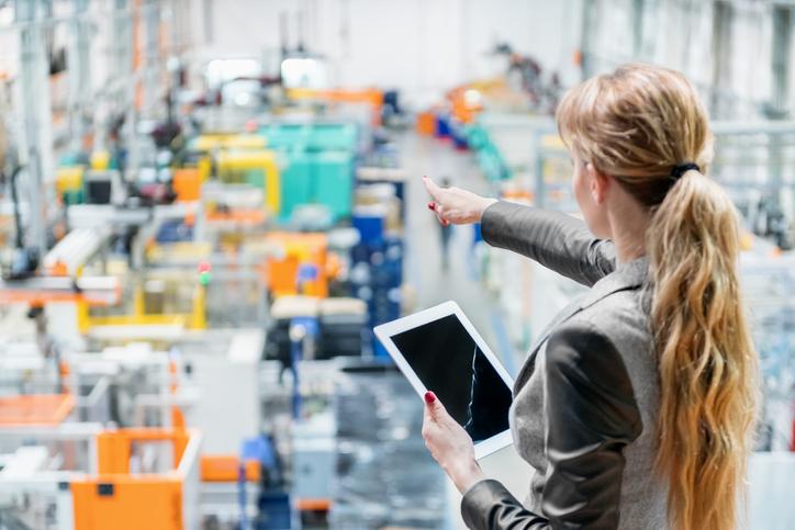 Frau von hinten, rechts im Anschnitt, mit blondem Pferdeschwanz, blickt auf eine Fabrikhalle, zeigt mir dem Finger der rechten Hand auf den Raum und hält in der linken Hand ein Tablet, auf dessen Bildschirm eine grafische Linie zu erkennen ist, die nach oben zeigt.