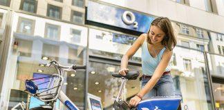 Fotoaufnahme von unten nach oben fotograftiert, zeigt ein Fahrrad von nextbike - erkennbar an einem Branding vor dem Hinterrad und dem Gepäckträger am Lenker. Rechts dahinter eine junge Frau in einem türkisfarbenen, sommerlichen Top, die das Schloß betätigt. Im Hintergrund ist ein Ladengeschäft mit O2 Logo zu erkennen.