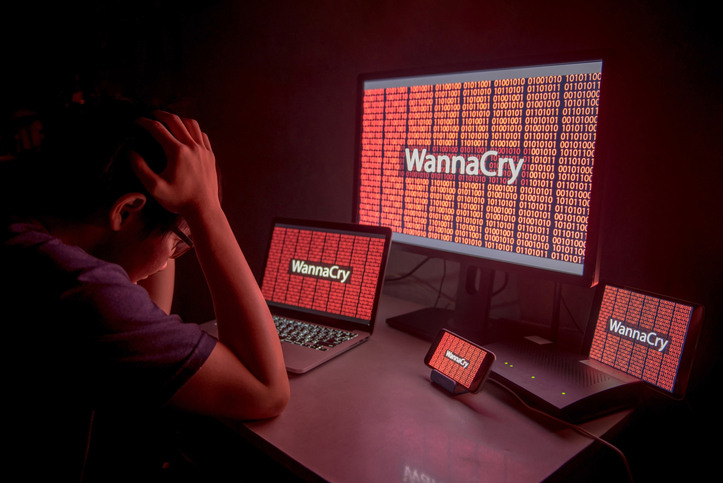 Mensch mit Brille, links im Anschnitt, stützt den Kopf in seine Hände: vor ihm vier verschiedene Monitore, unterschiedlicher Größe, auf denen zwischen einer roten 0-1-Zahlenfolge der Begriff WannaCry zu sehen ist.