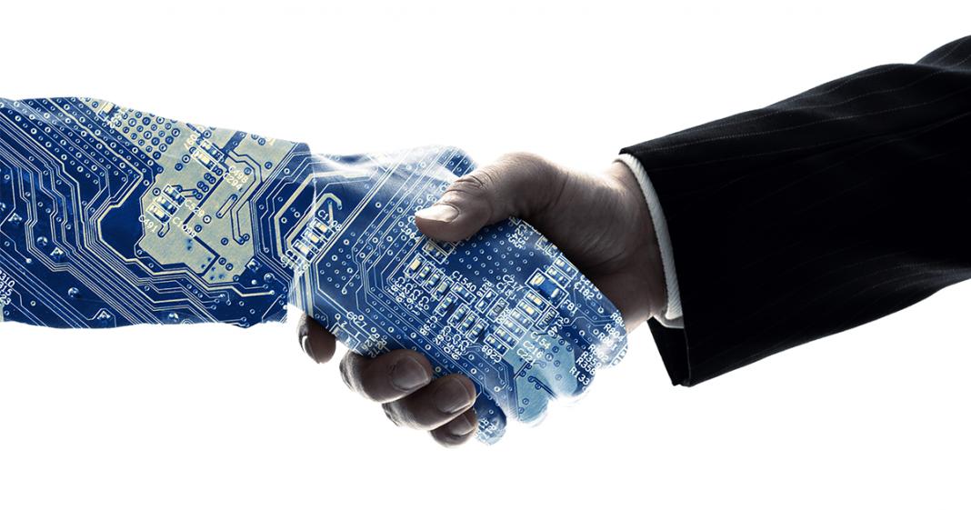 Roboterarm und Menschenarm geben sich die Hand