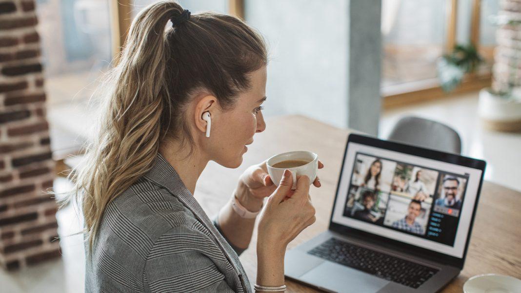 Frau sitzt zu Hause am Laptop und tirnkt einen Cafe